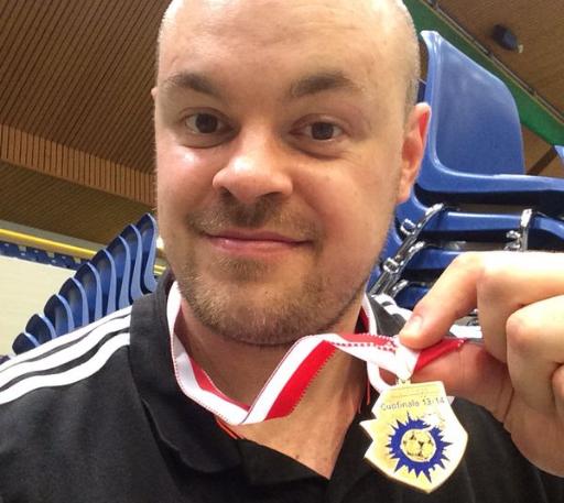 Handball-Spieler Markus Krauthoff zeigt seine Medaille in die Kamera.