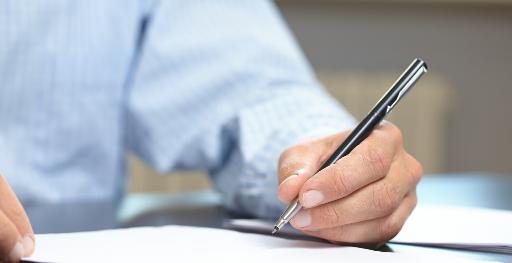 Männerhand schreibt auf einem Blatt Papier.